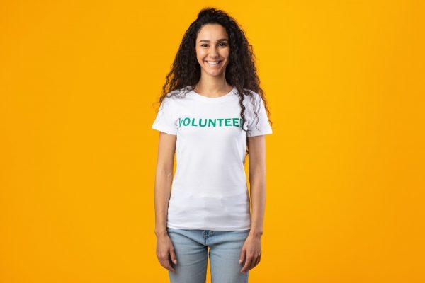 Smiling Volunteer Woman Wearing White T-Shirt Standing On Yellow Background
